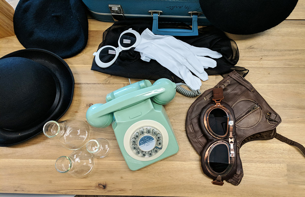 Signature props for a brand photoshoot including a retro phone, old-timey airplane pilot goggles